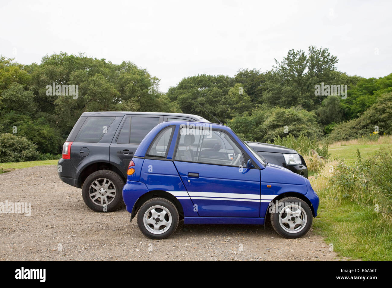 Electric car next to four wheel drive - Stock Image