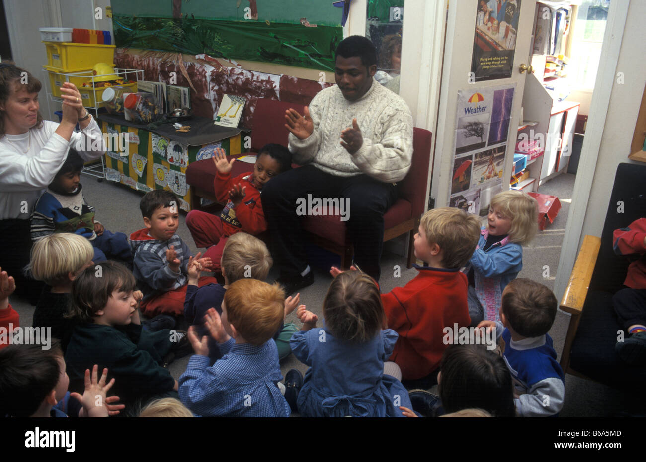 ethnic male teacher with class of small children at playgroup with the children all clapping their hands - Stock Image