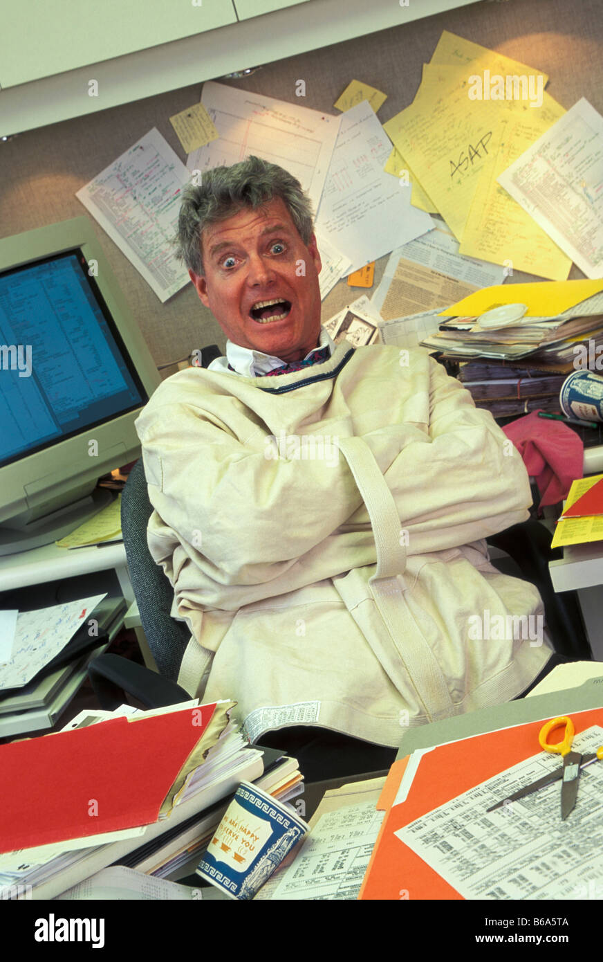 crazy businessman in straight jacket at desk stock photo 21122426