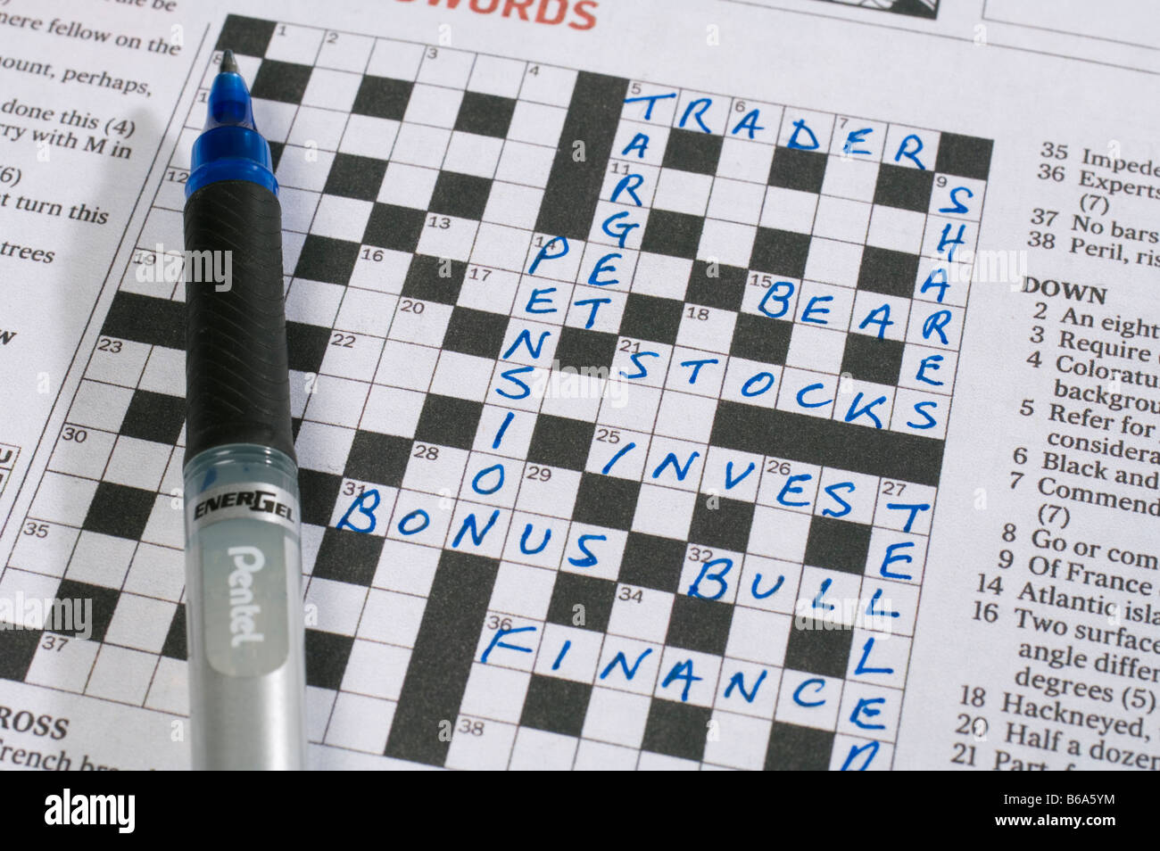 A Crossword Puzzle In Newspaper With Words Relating To Business And Stocks Shares Investments