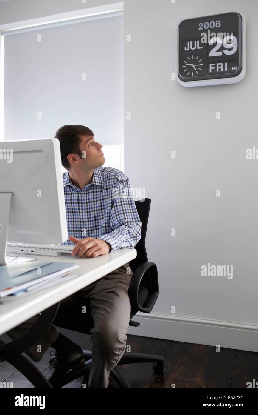 Office worker looking at clock - Stock Image