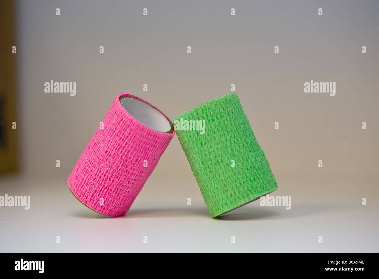 Pink and green rolls medical tape propped against each other against white/gray background - Stock Image