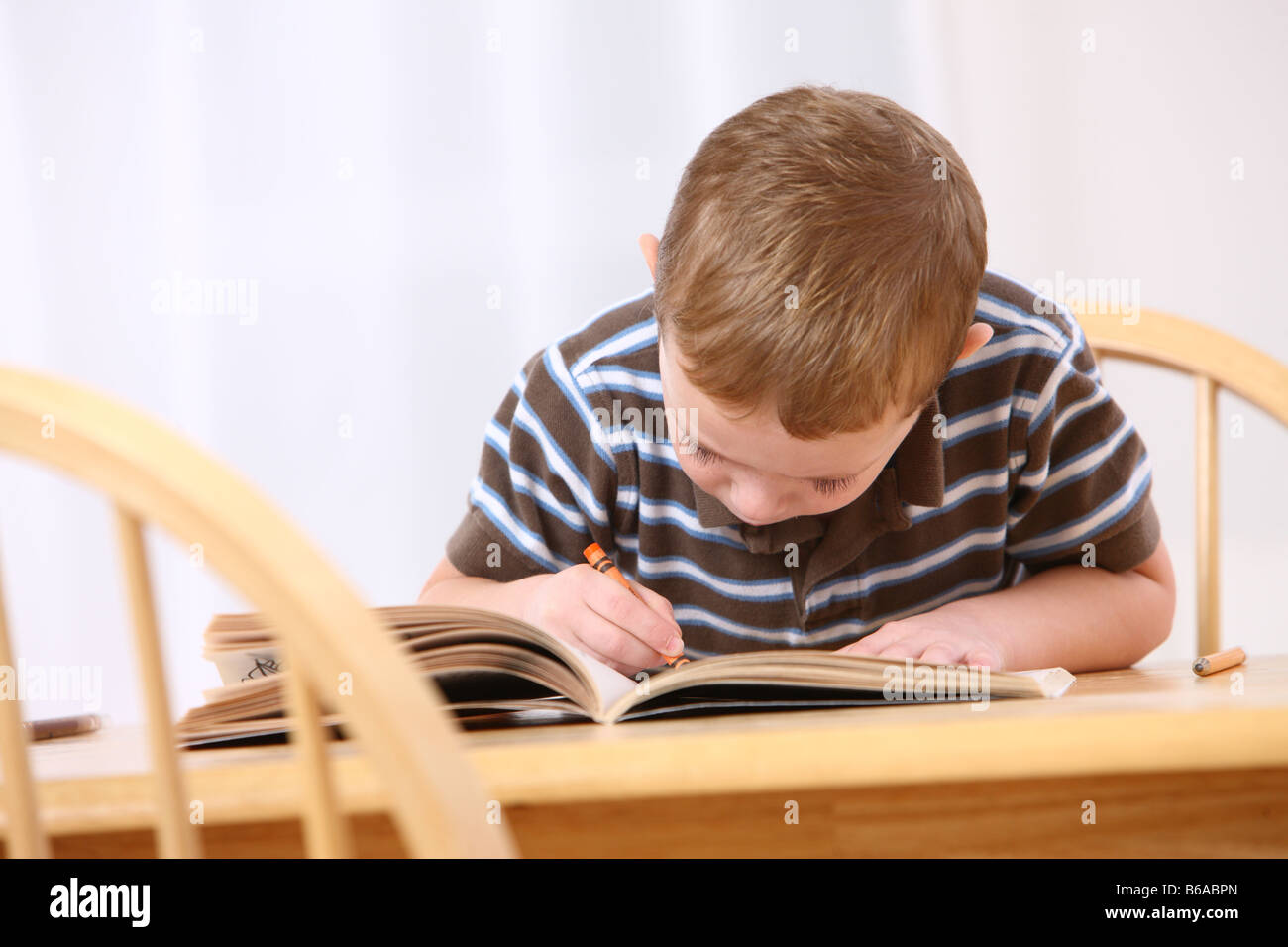 Young Boy Sitting At Table Coloring Book