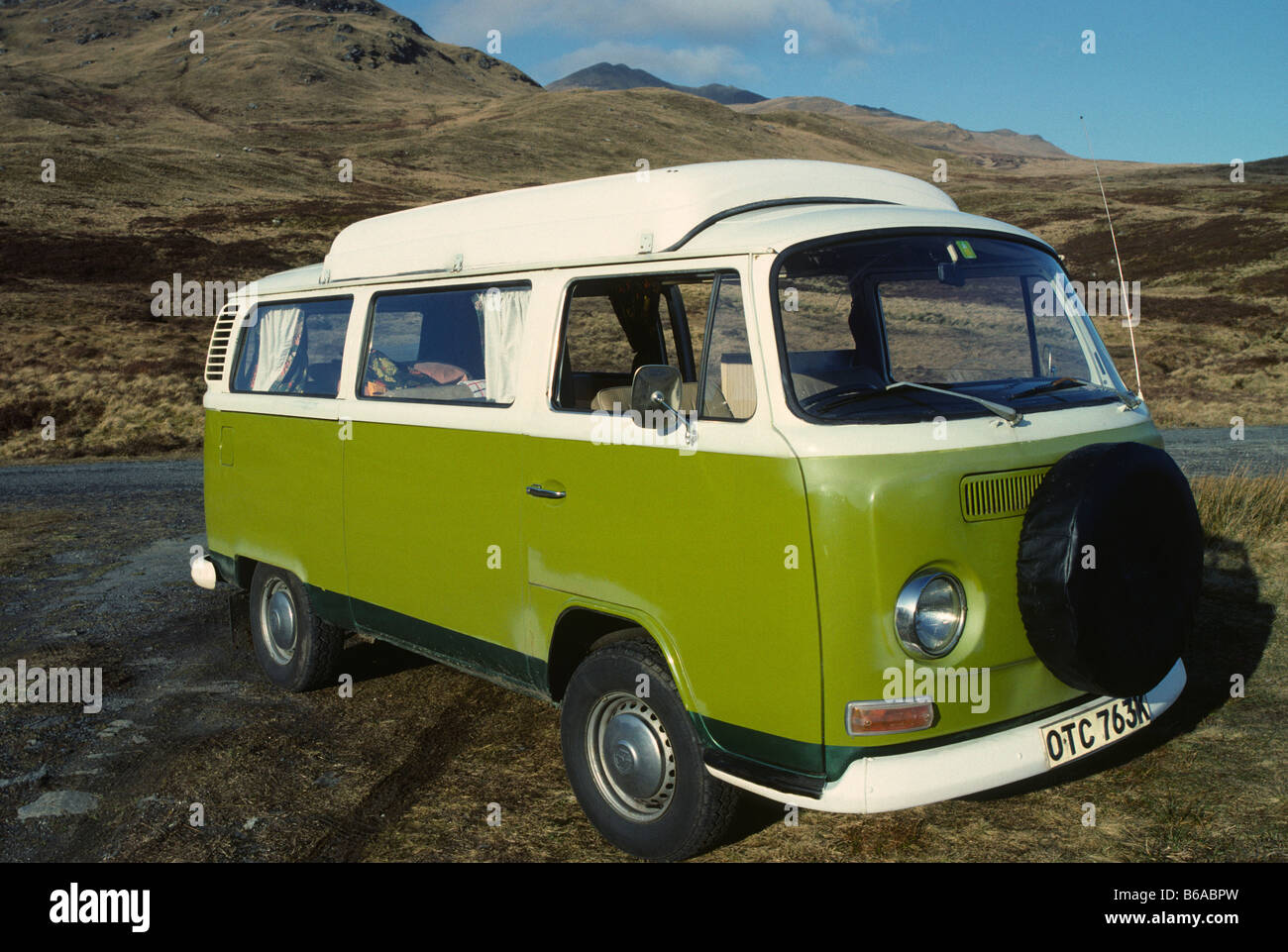 A green VW Type Two camper van.  British registered, right hand drive with side elevating roof - Stock Image
