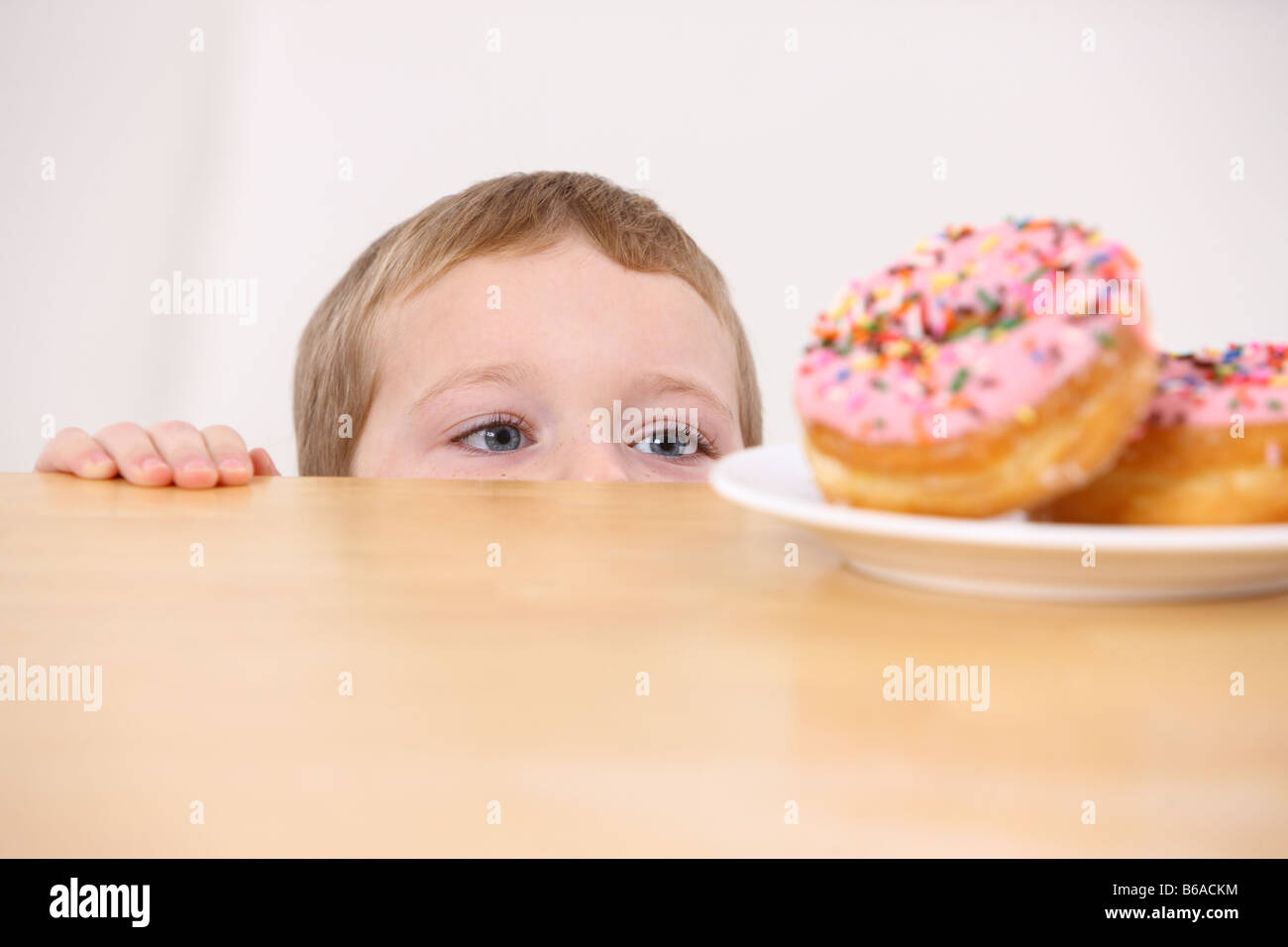 Young boy peeking over table at plate of doughnuts - Stock Image