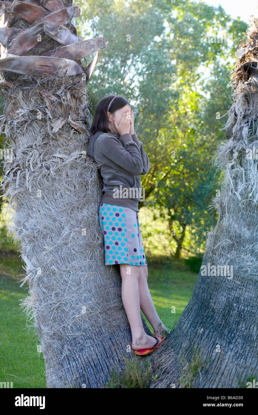 Young girl playing hide and seek - Stock Image