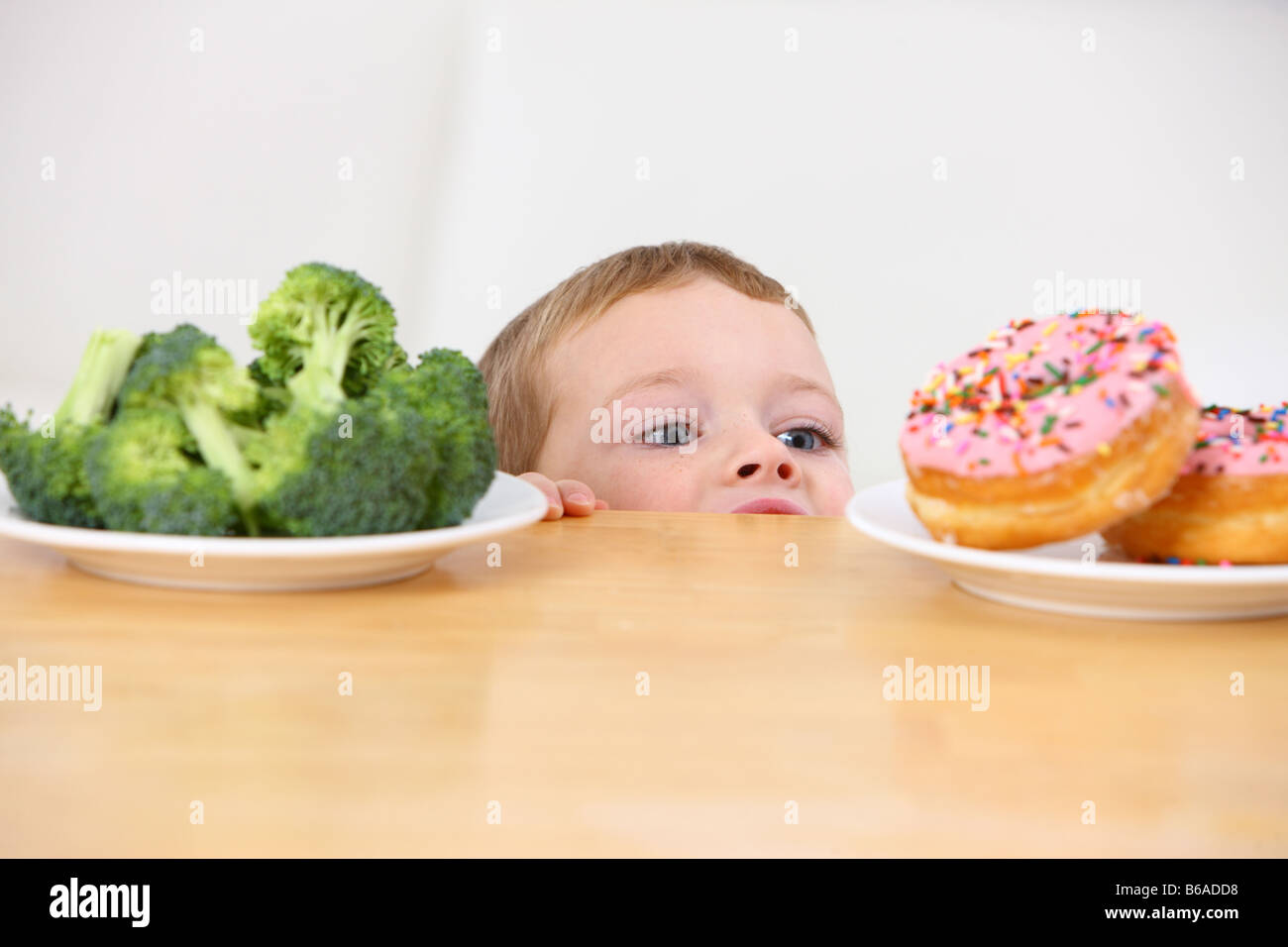 Young boy peeking over table at plates of donuts and broccoli - Stock Image
