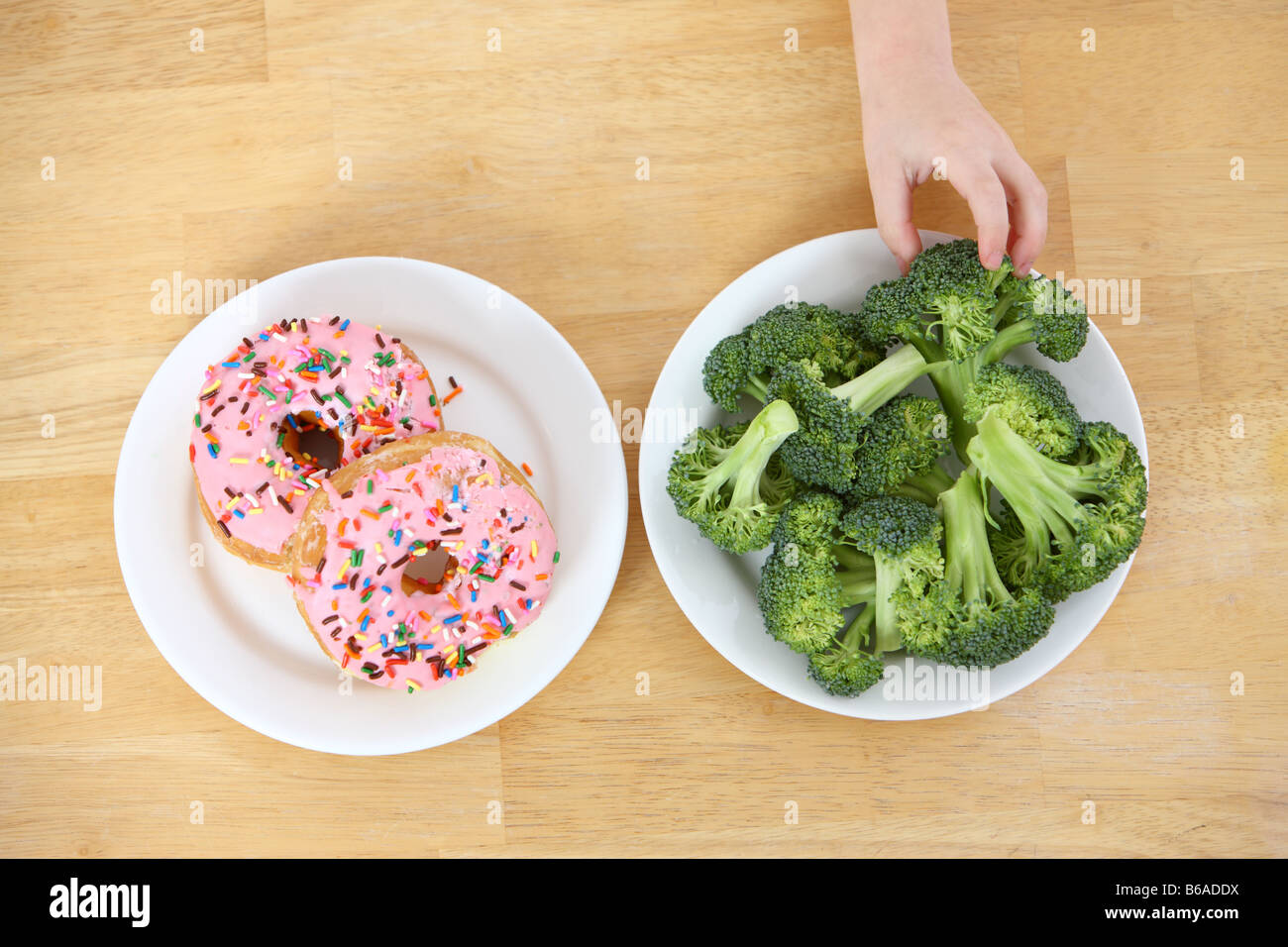Child s hand reaching for healthy broccoli rather than doughnuts - Stock Image