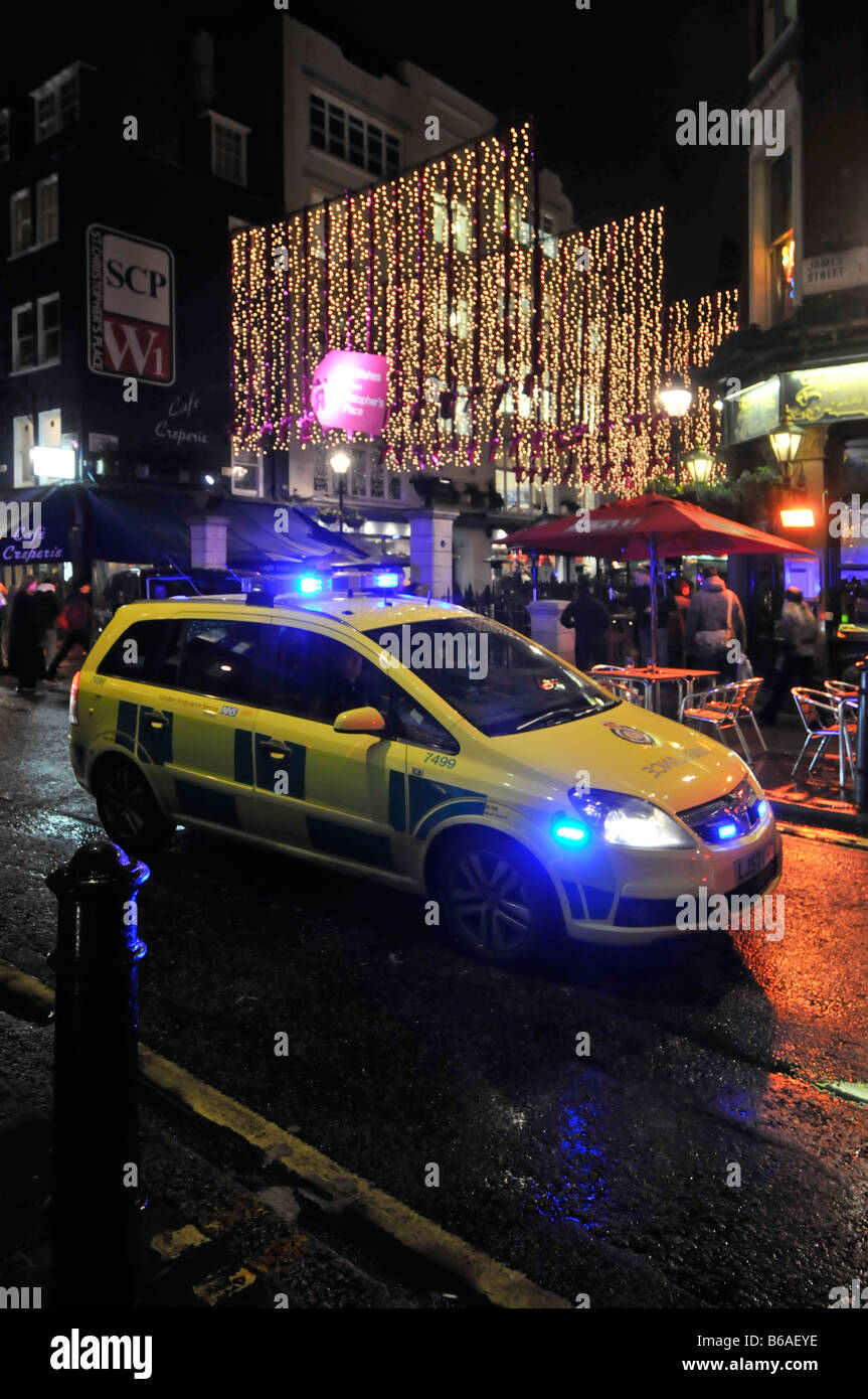 London West End ambulance car on emergency 999 call stuck in rush hour traffic blue lights at Christmas time - Stock Image