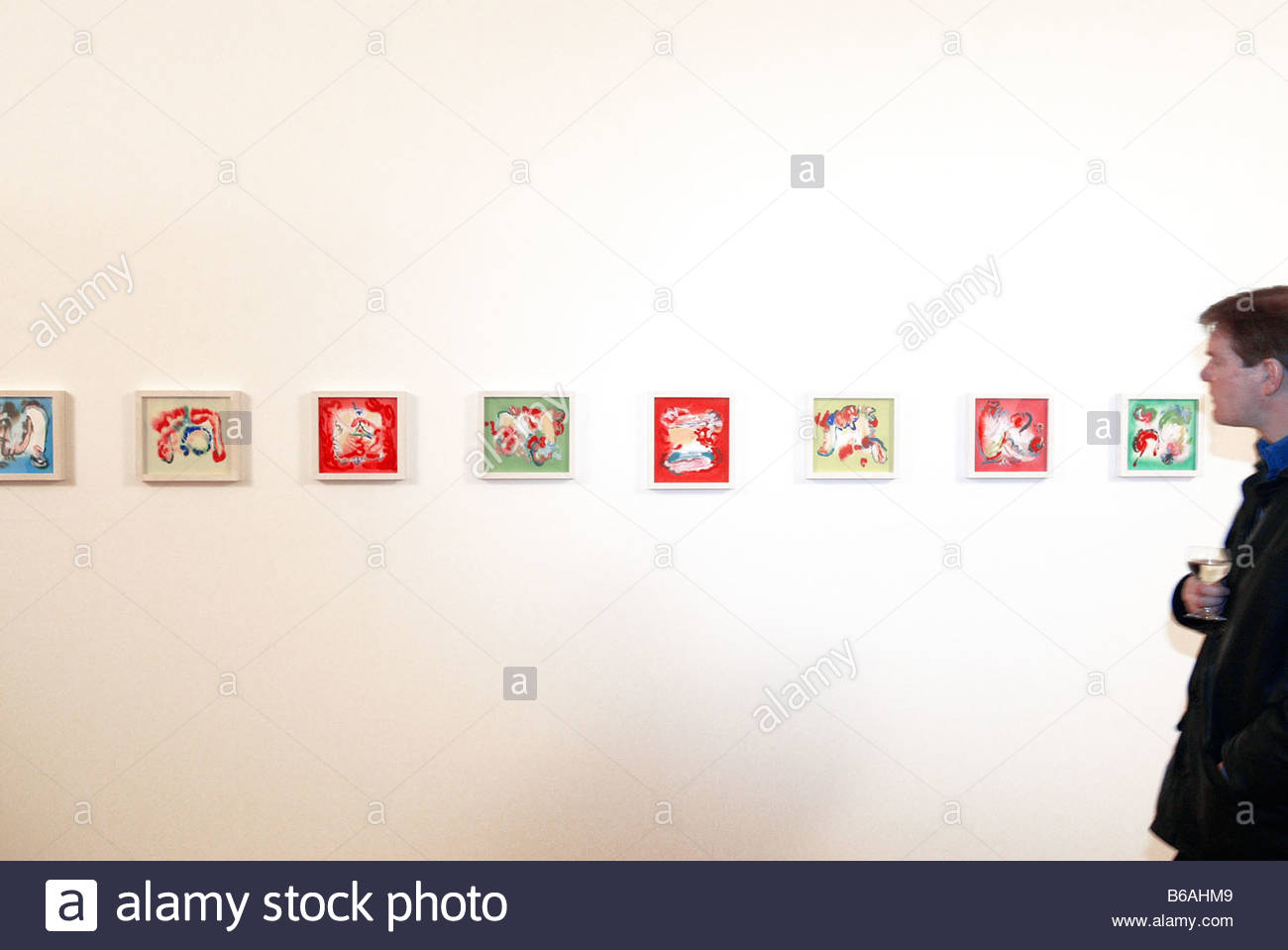 Man looking at paintings in an art gallery - Stock Image