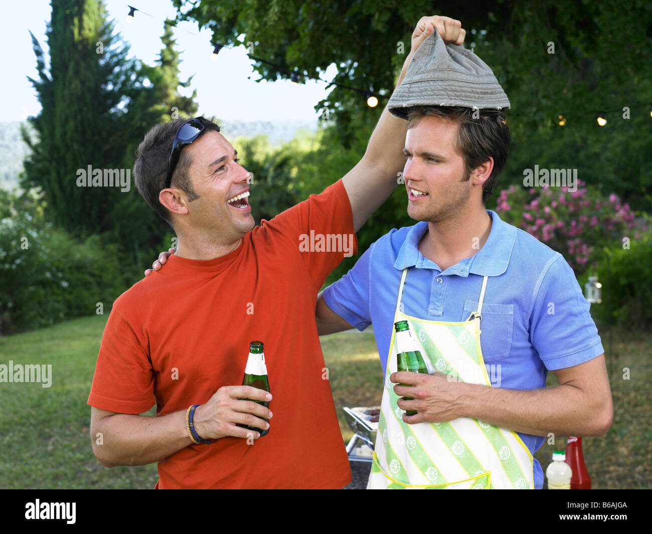Two men laughing at barbecue - Stock Image