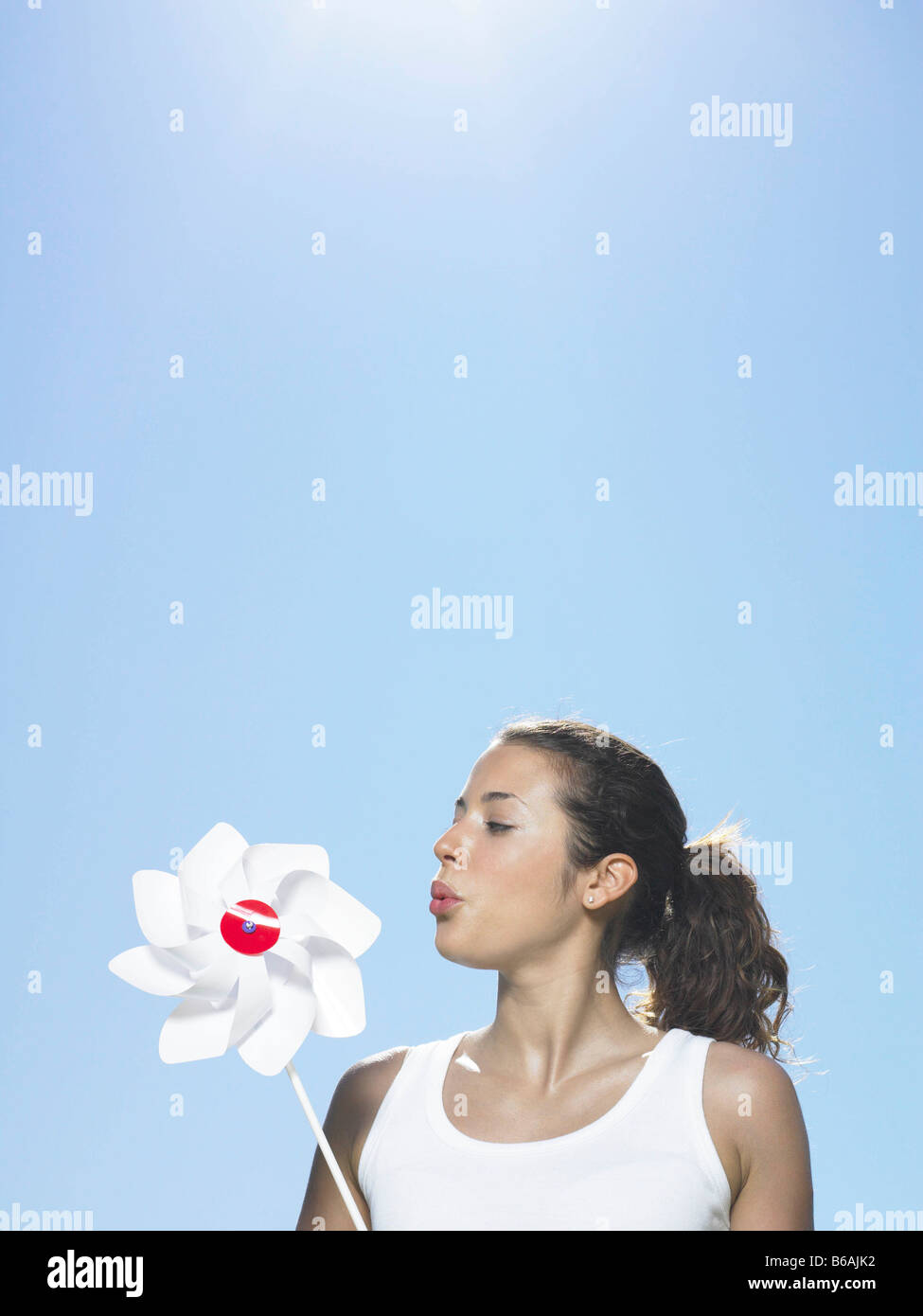 Girl blowing windmill in sun - Stock Image