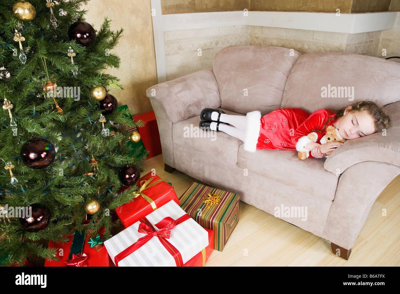 Girl (6-7) sleeping on sofa by Christmas tree - Stock Image