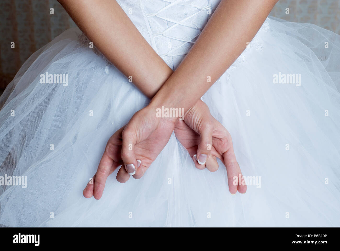 Brides fingers crossed behind back, mid section - Stock Image