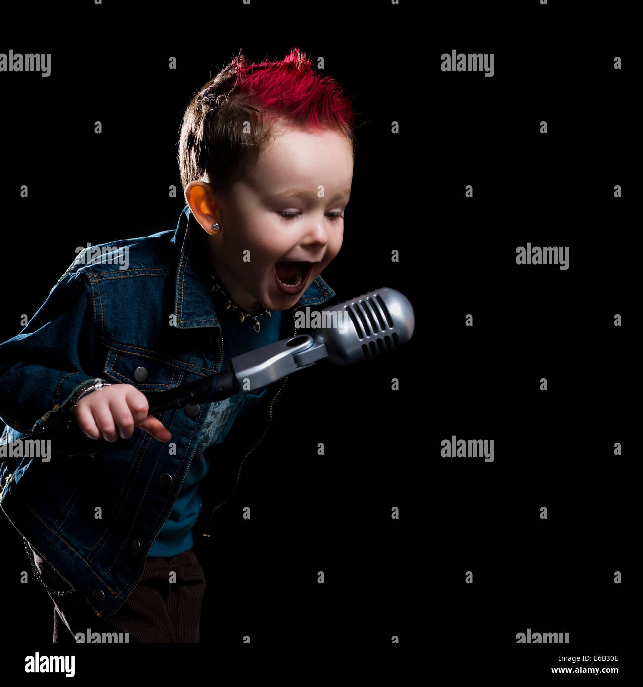 little boy singing into a microphone - Stock Image