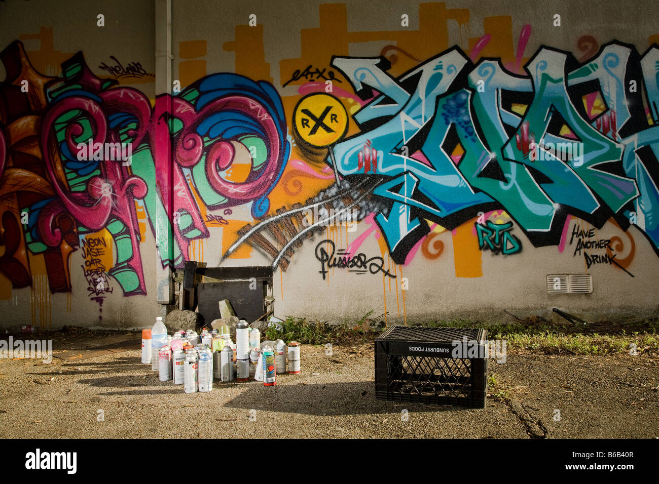 Graffiti art and Spray cans in an Alley - Stock Image