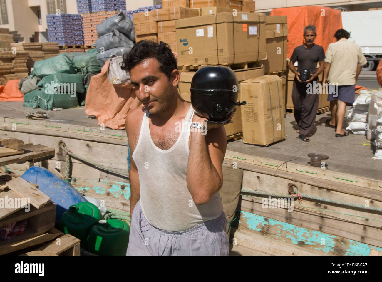 A worker in Dubai Creek loading small engines on a ship which will leave for Iran that same night despite international Stock Photo