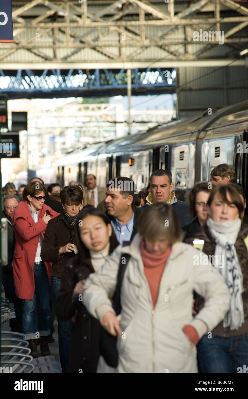 Passengers getting off of a train onto a crowded railway station platform in the uk - Stock Image