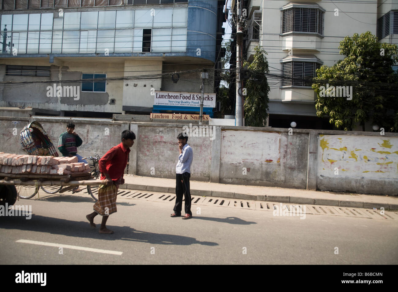 A rickshaw puller pulling a cart full of bricks in Dhaka - Stock Image