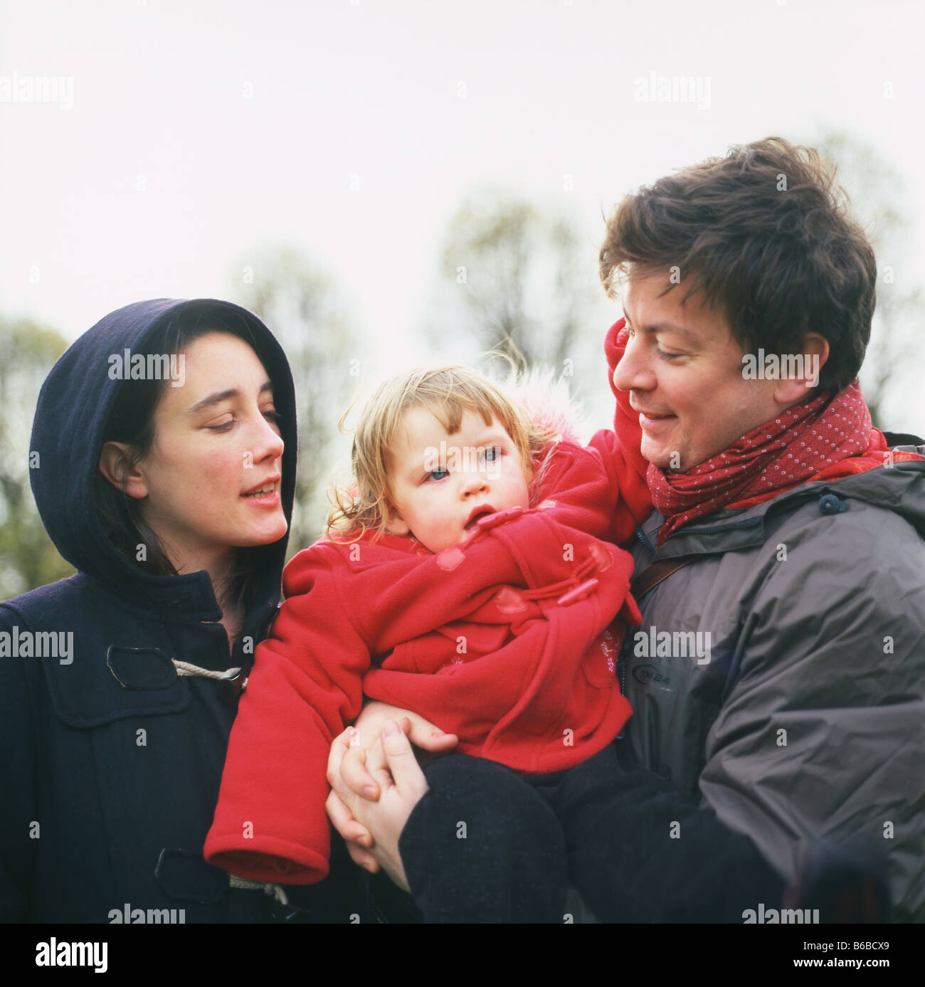 A London couple with a young child wearing winter clothing in a park in Walthamstow, London, England KATHY DEWITT - Stock Image
