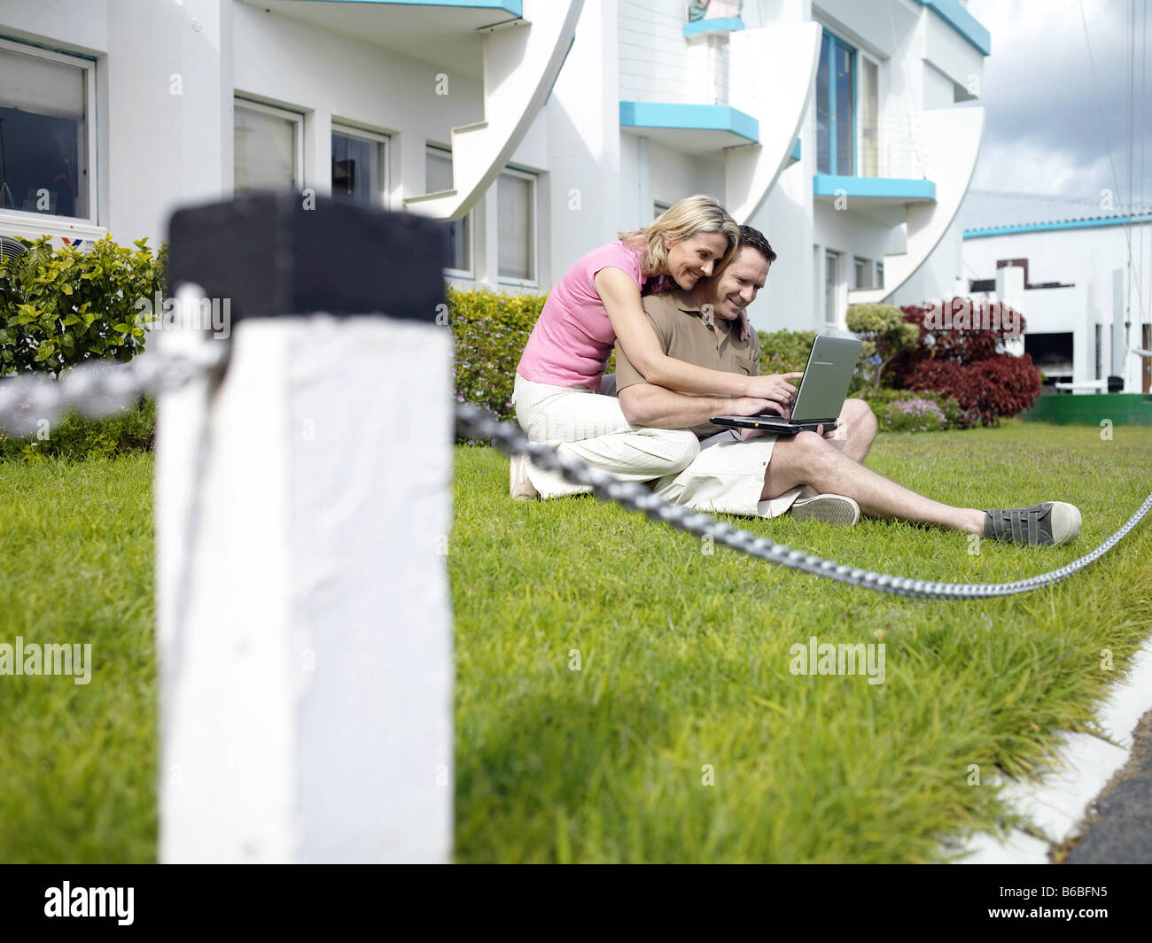 Couple using laptop at front yard - Stock Image