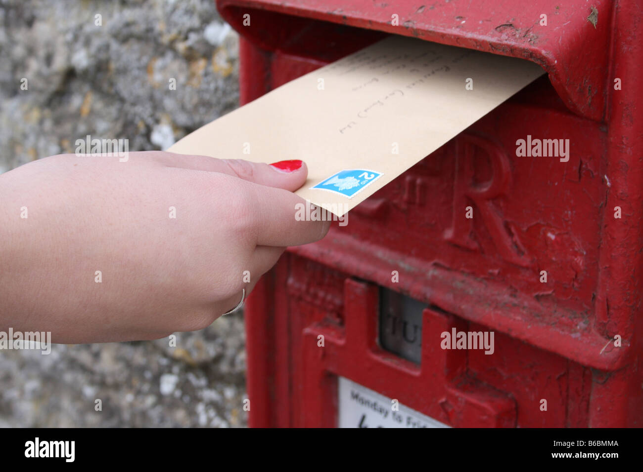 Posting a letter in an Royal mail post box. - Stock Image