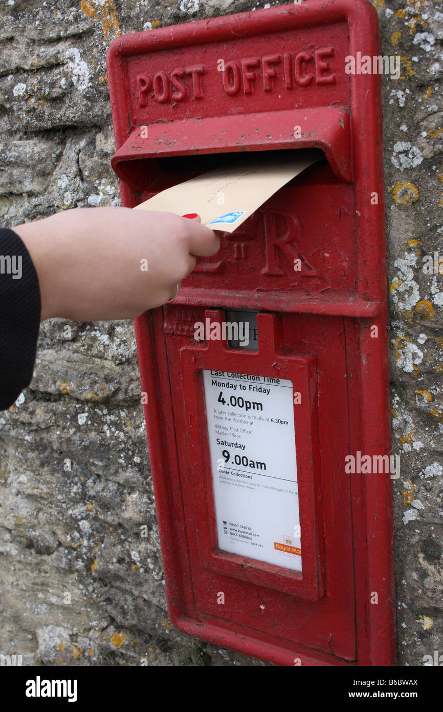 Posting a letter in an Royal mail post box. Stock Photo
