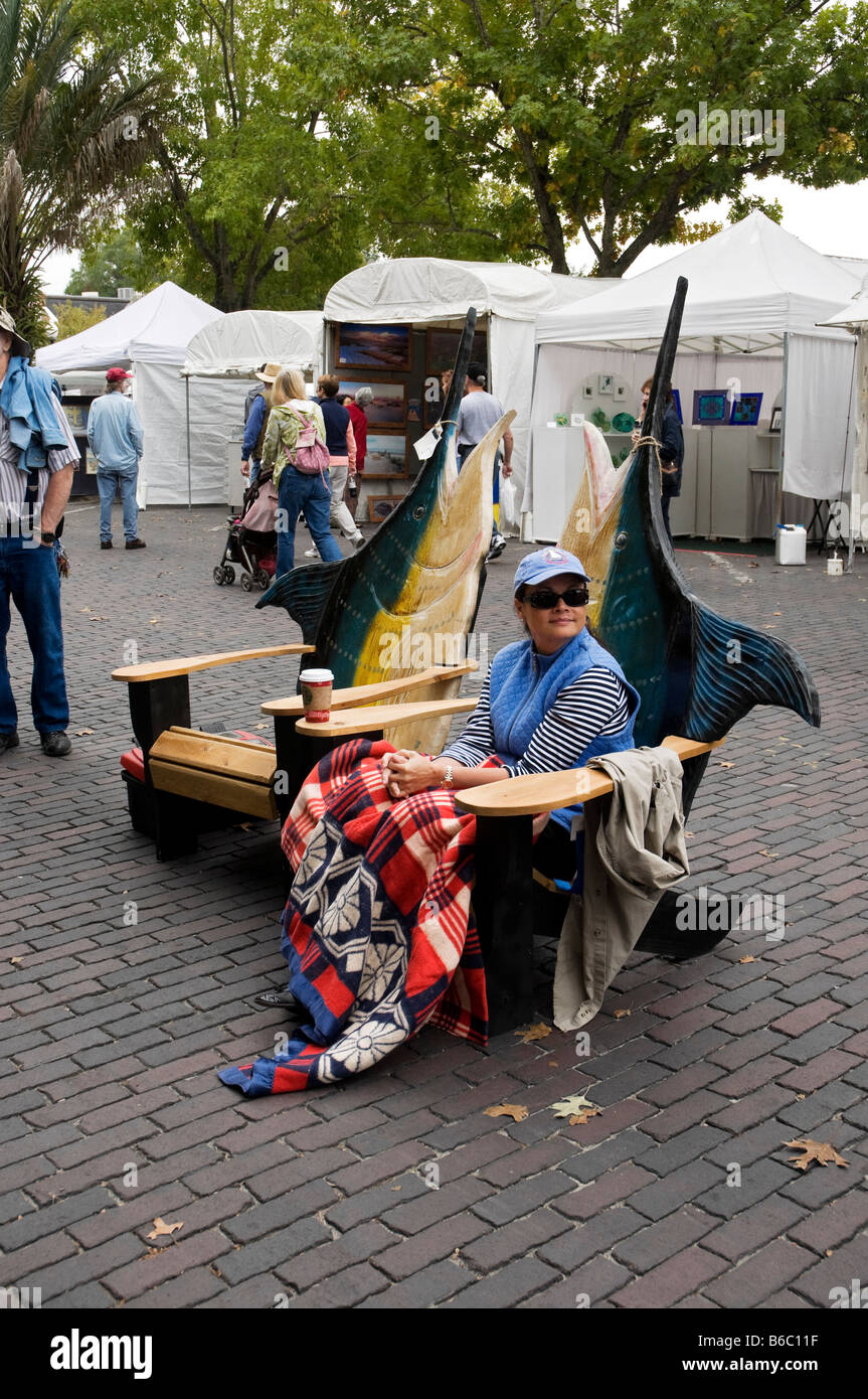 woman sits in custom made outdoor furniture in shape of giant marlin