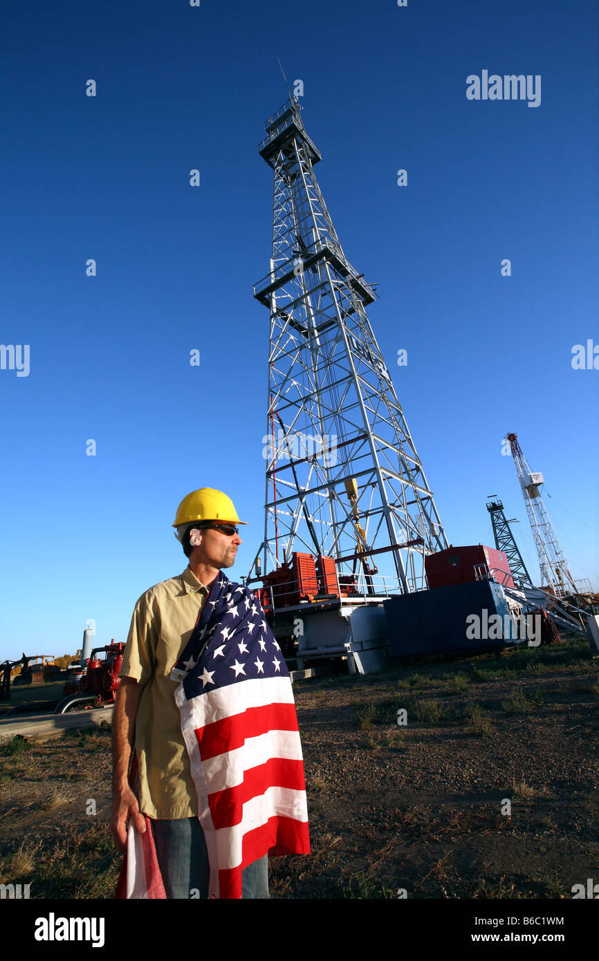 45 year old rig worker with USA flag draped over shoulder at drill rig - Stock Image