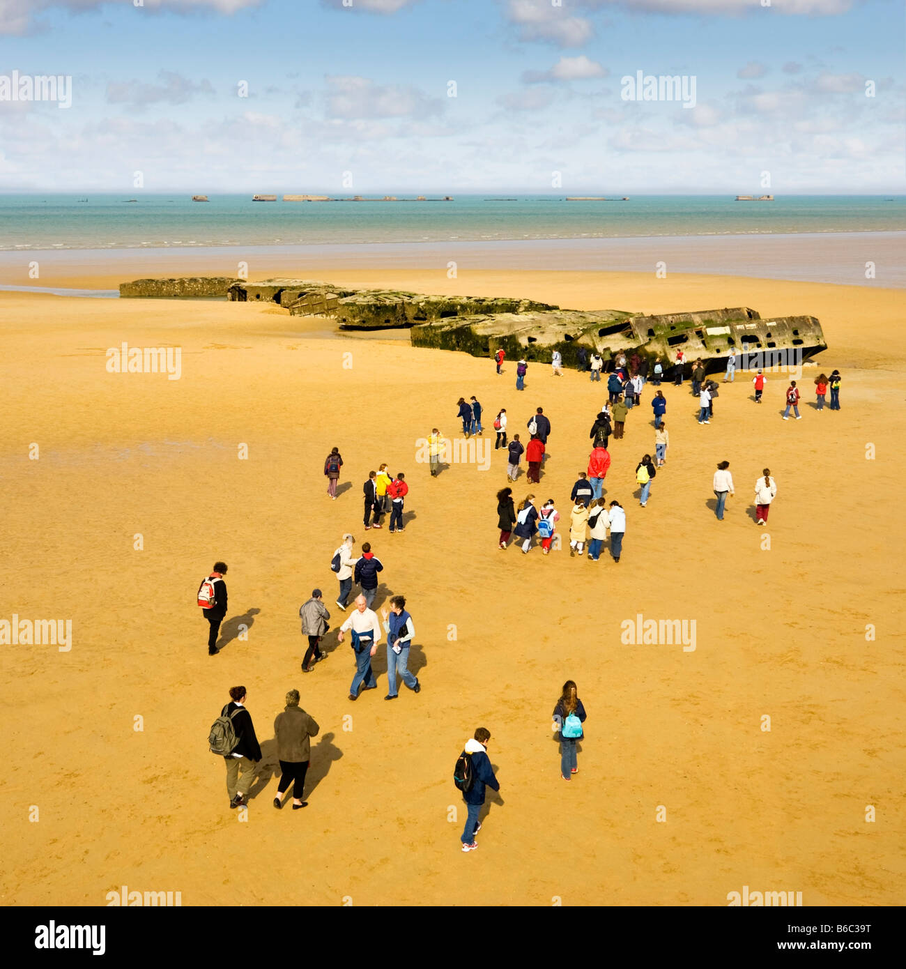 School trip visit to the World War 2 Mulberry harbour remains on the beaches at Arromanches Les Bains, Normandy, - Stock Image