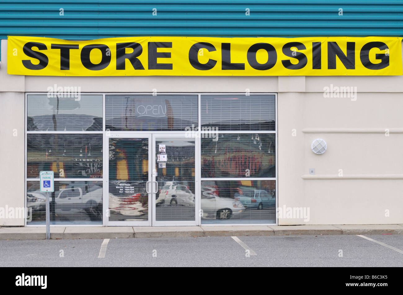 Store Closing Banner across storefront of empty retail store. USA - Stock Image