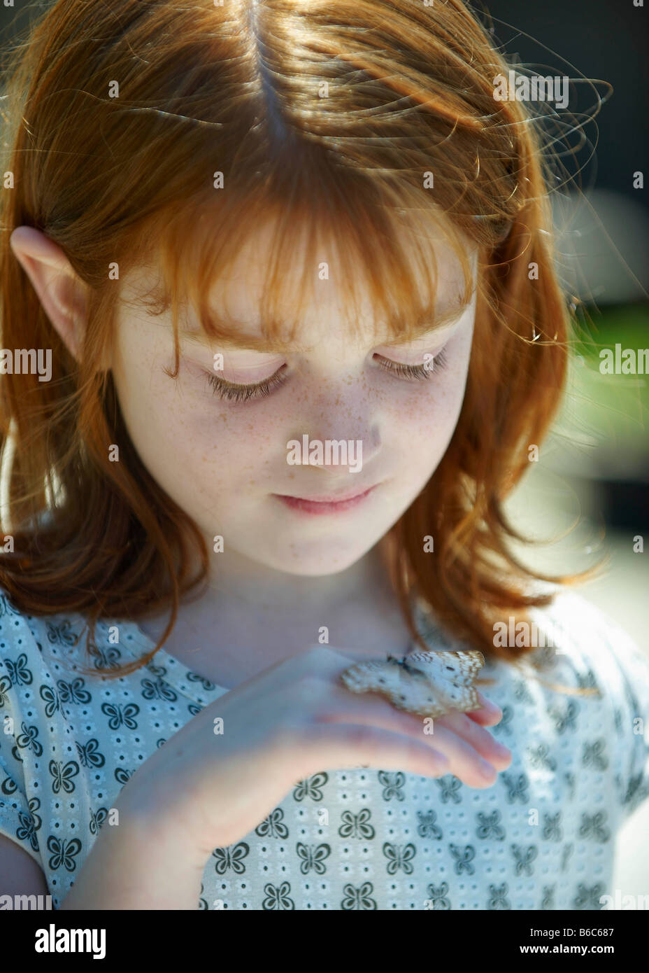 Young girl looking at butterfly - Stock Image