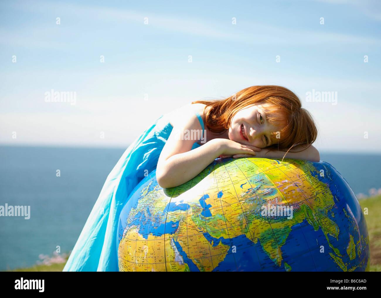 Young girl lying on inflatable globe - Stock Image