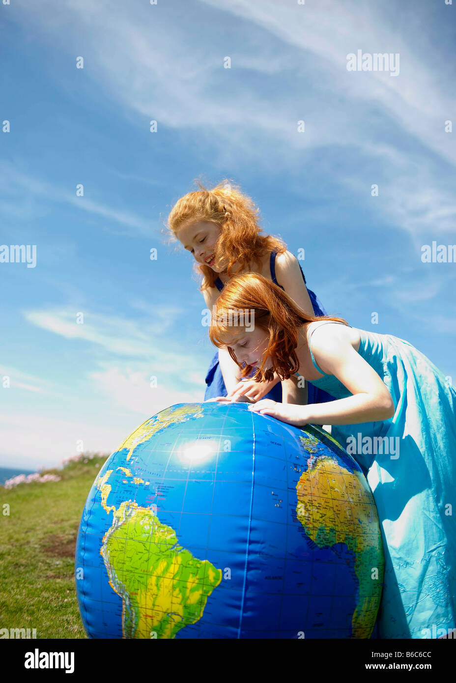 2 girls looking at inflatable globe - Stock Image