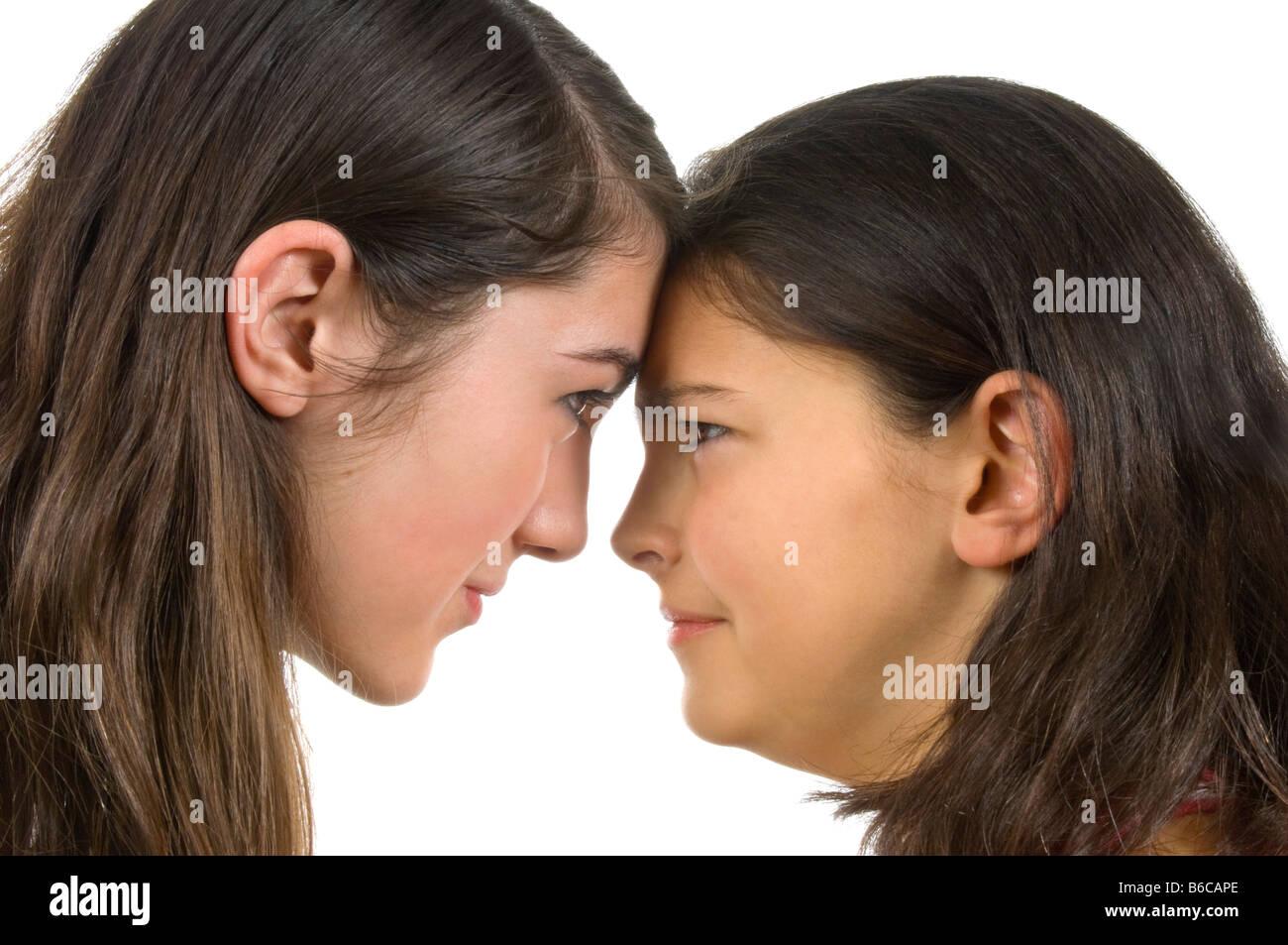 Horizontal portrait of two teenage sisters having an ...