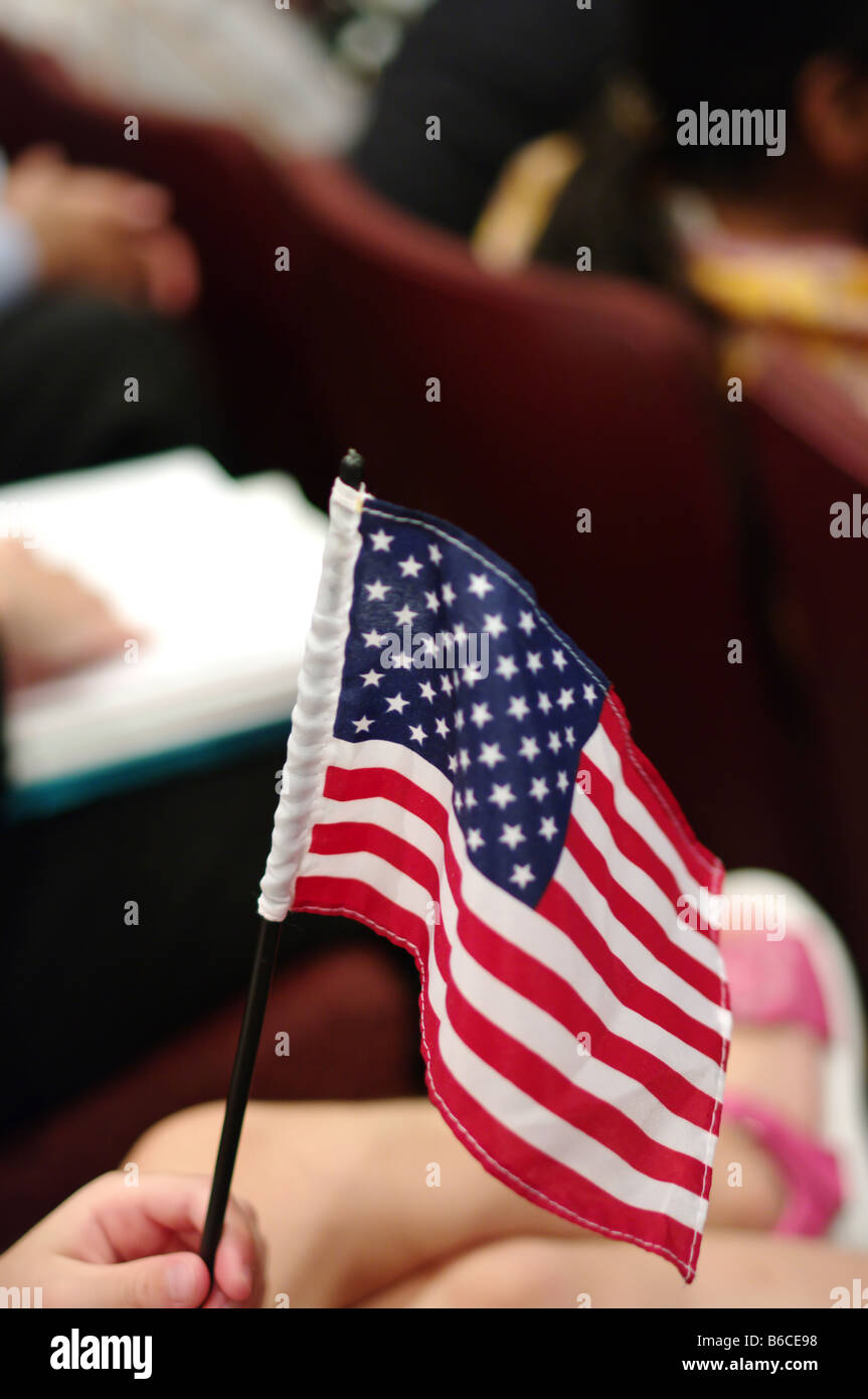 American flag in girl hand at citizenship ceremony - Stock Image