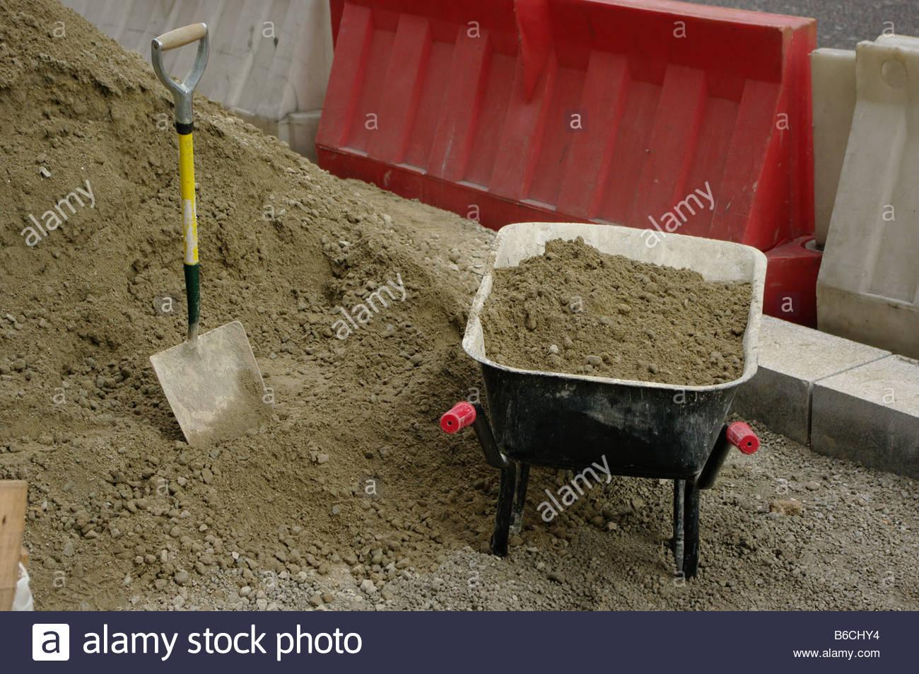 Shovel spade wheelbarrow sand London England Street road building digging hole construction tool tools Stock Photo