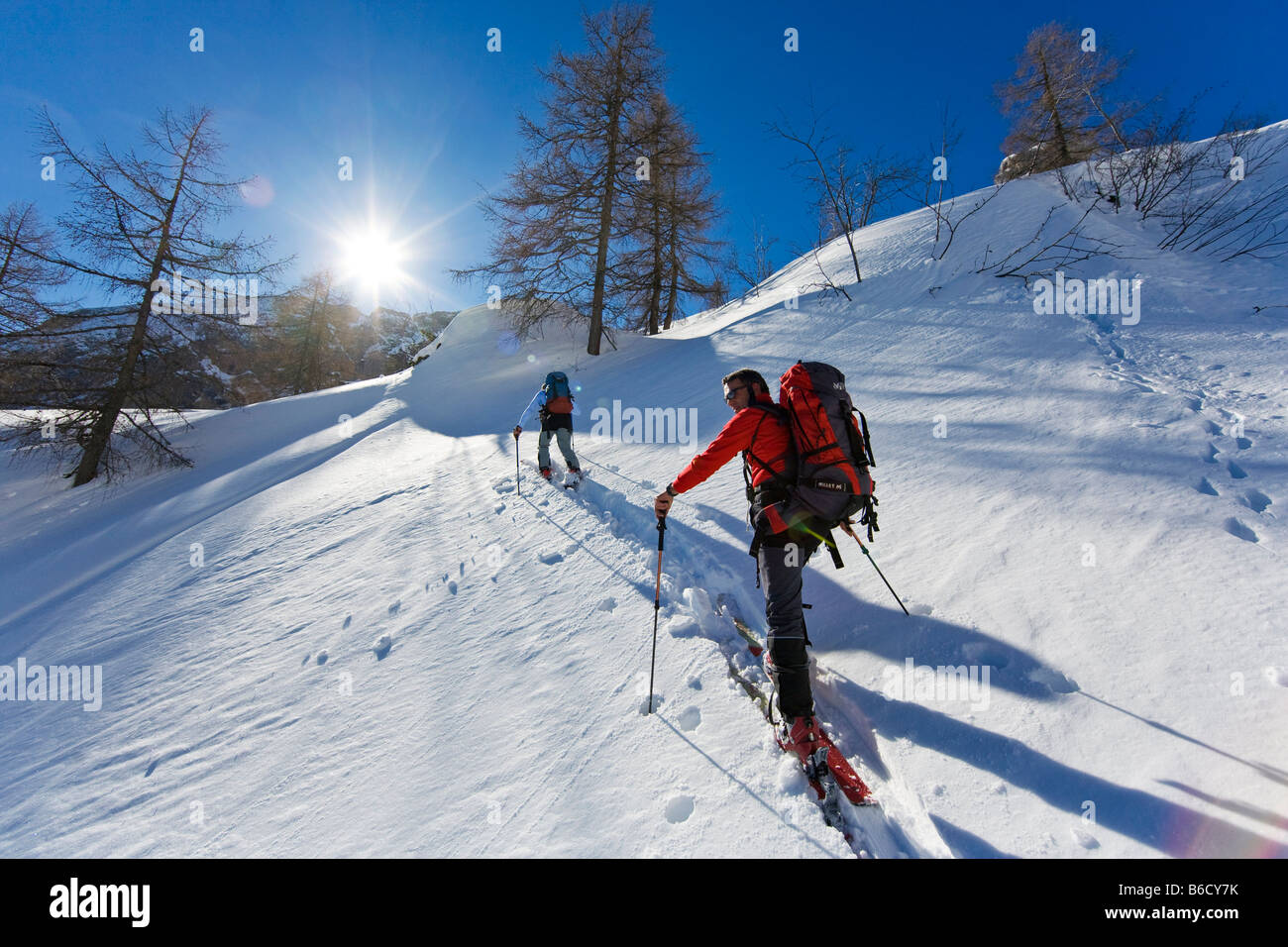 Two skiers walking with skis on snowcovered mountain, Knallstein, Tennengebirge, Tennengau, Salzburg, Austria - Stock Image