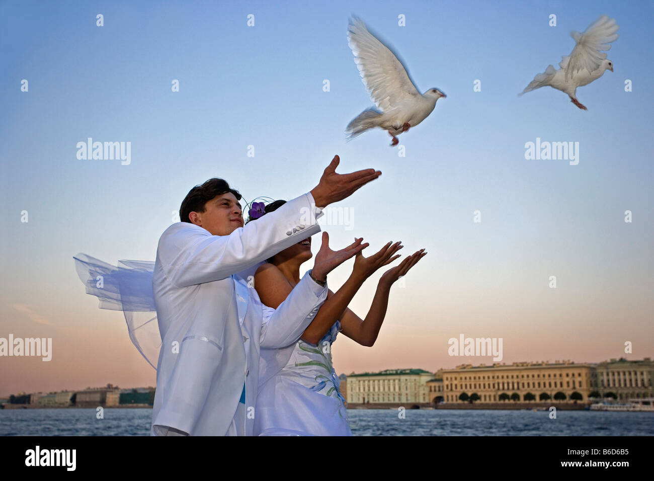 Russia, Saint Petersburg, Neva river. Hermitage background. Couple celebrate their marriage with white pigeon. - Stock Image
