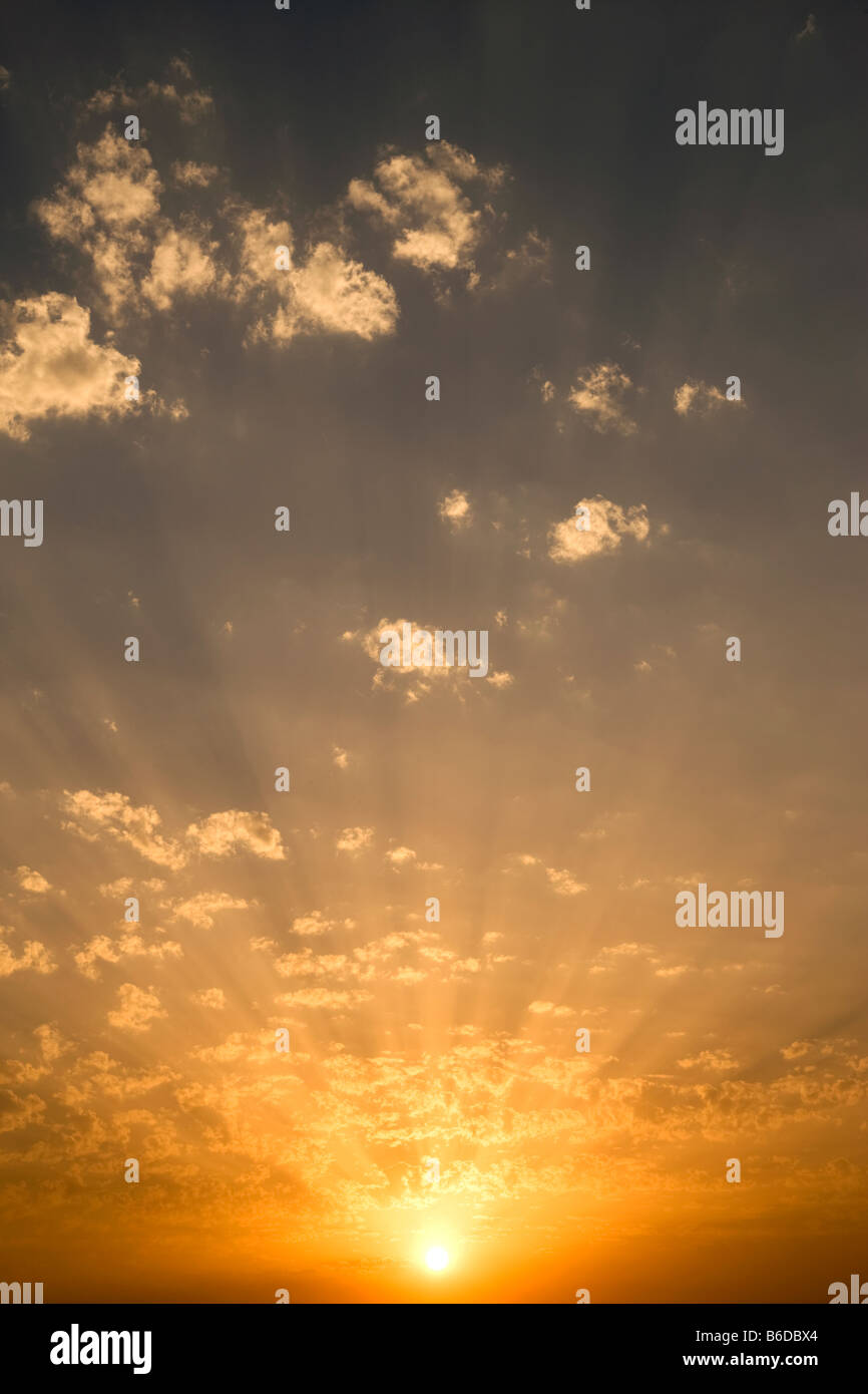 CLOUDSCAPE OF SUN LIGHT RAYS THROUGH BACKLIT PUFFY CLOUDS ON YELLOW SKY - Stock Image