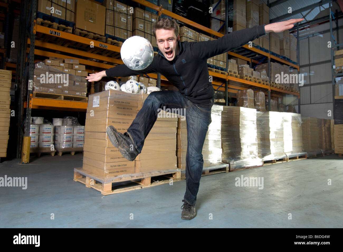 A man in a warehouse kicking one of the Fairtrade footballs he has imported for sale in Britain. - Stock Image