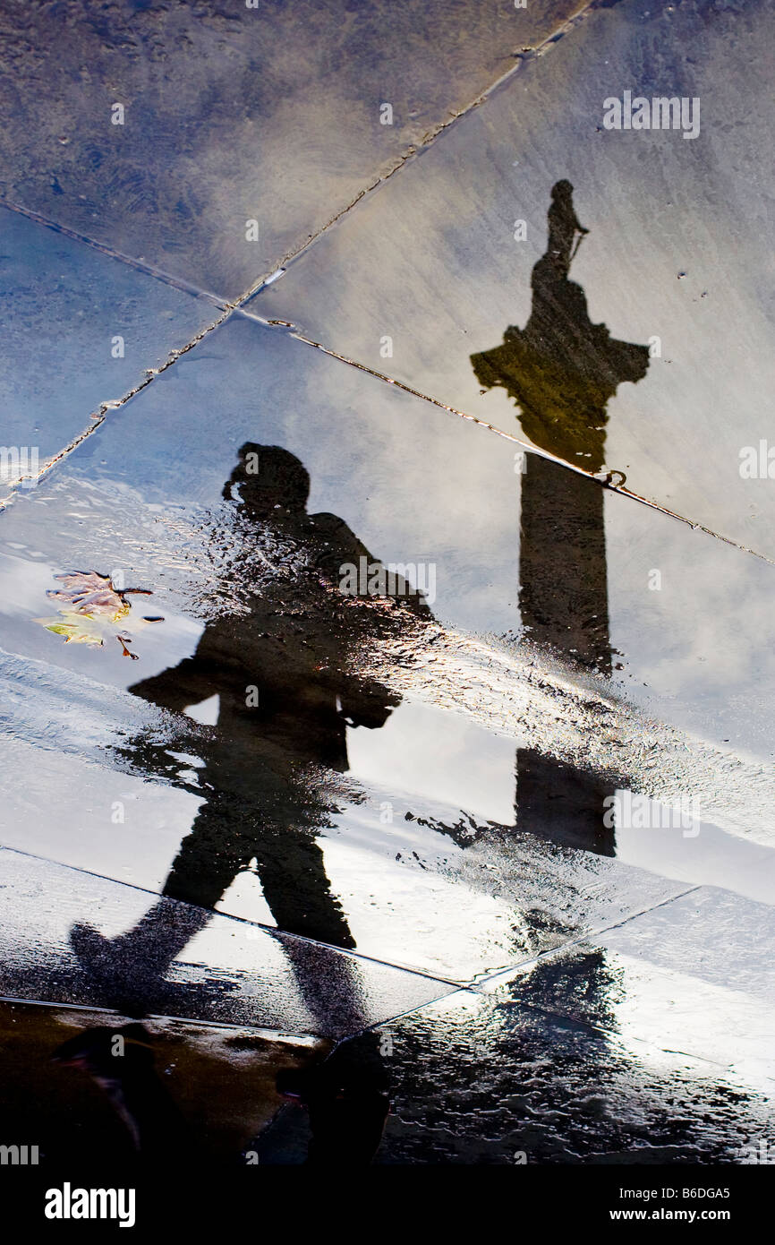 Nelsons Column and figure reflected in puddles. Trafalgar Square, London, England, UK - Stock Image