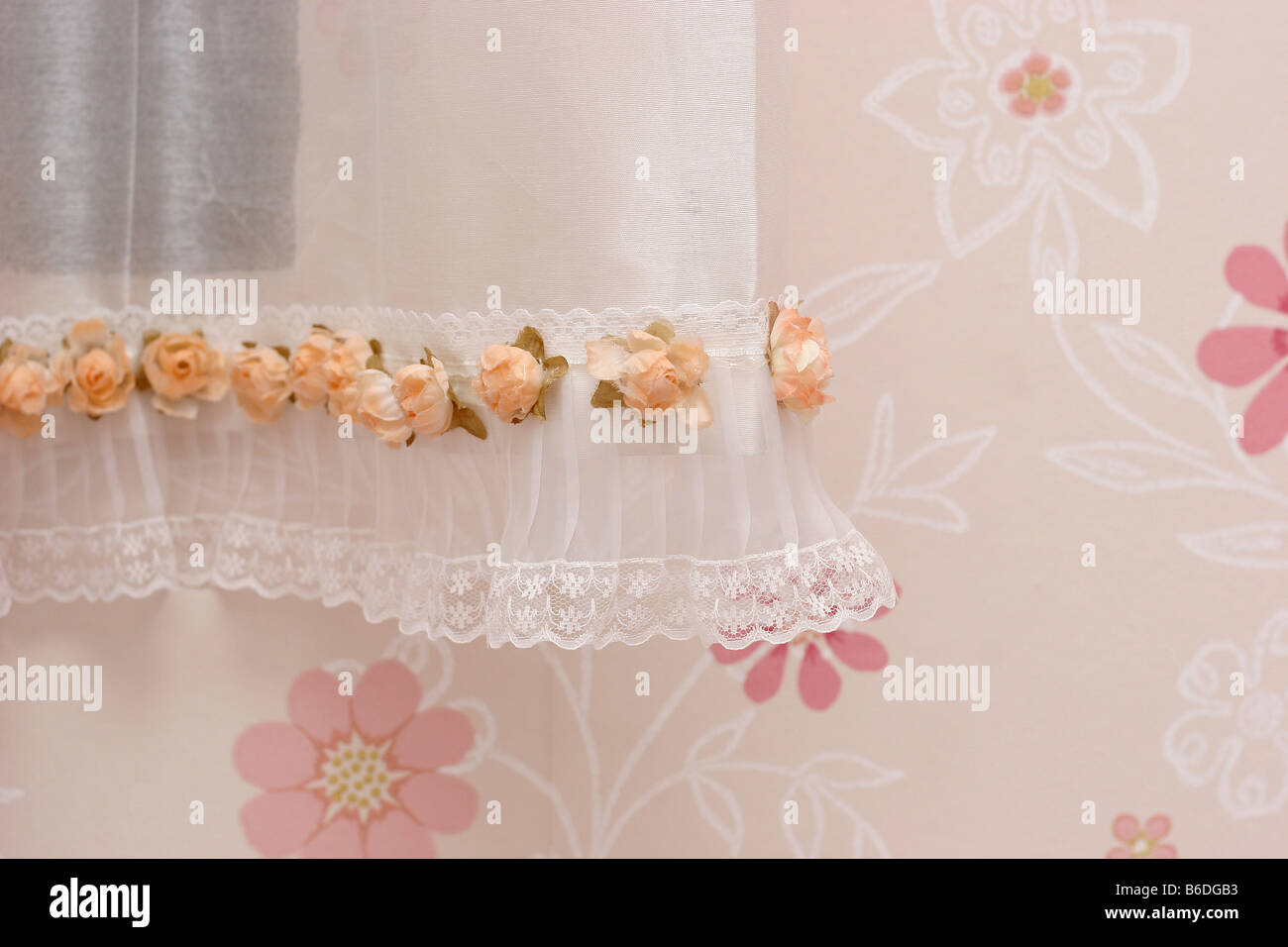 white Curtains on a window with a floral wall - Stock Image