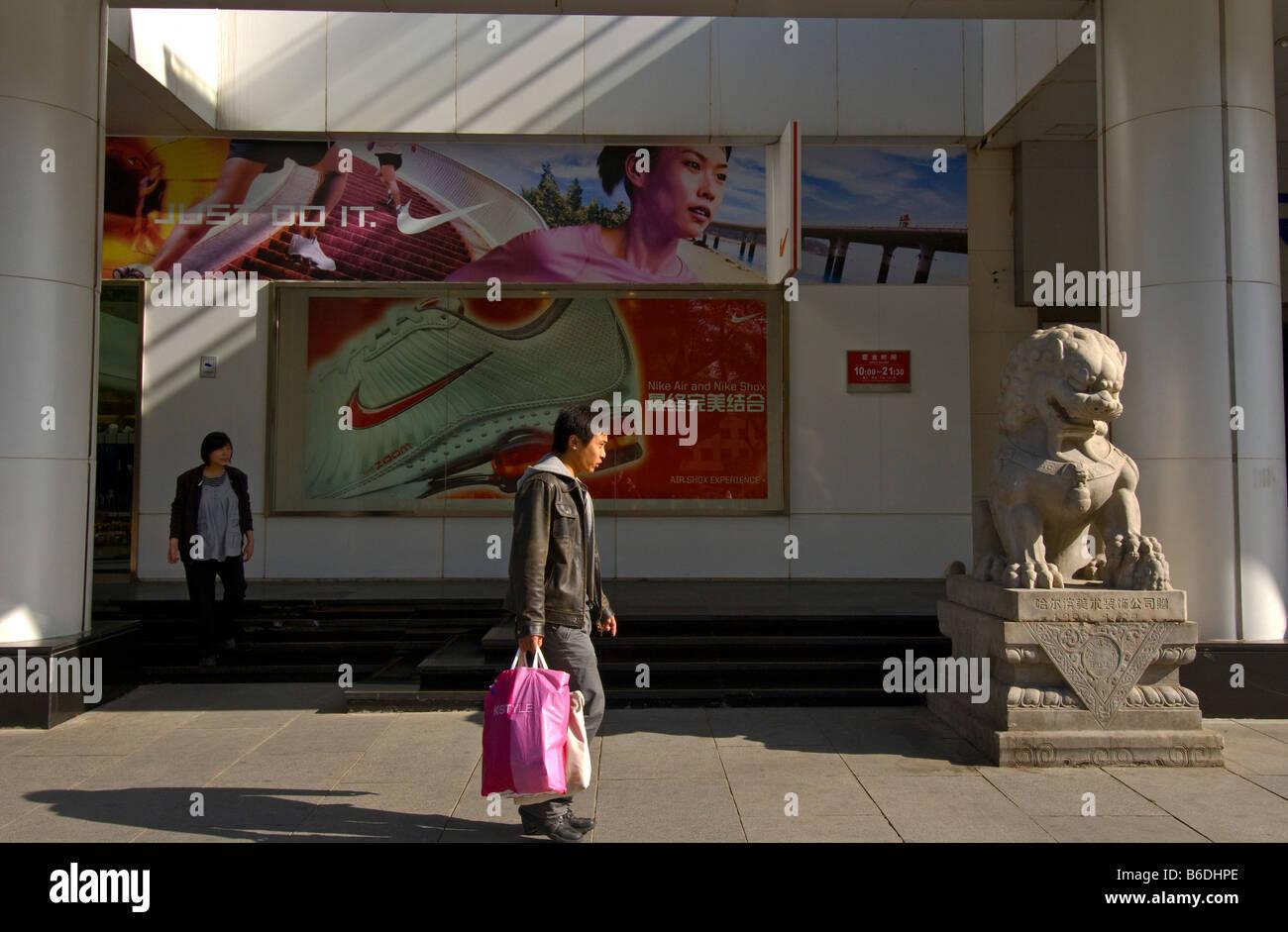 Shopper in front of Nike Advertising Avenue Bidajie Xidan Beijing China - Stock Image