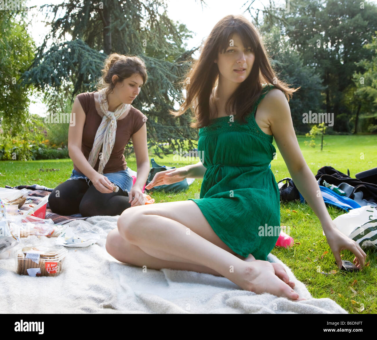 Two young women sitting down, having a picnic in Hyde Park (London, England) - Stock Image