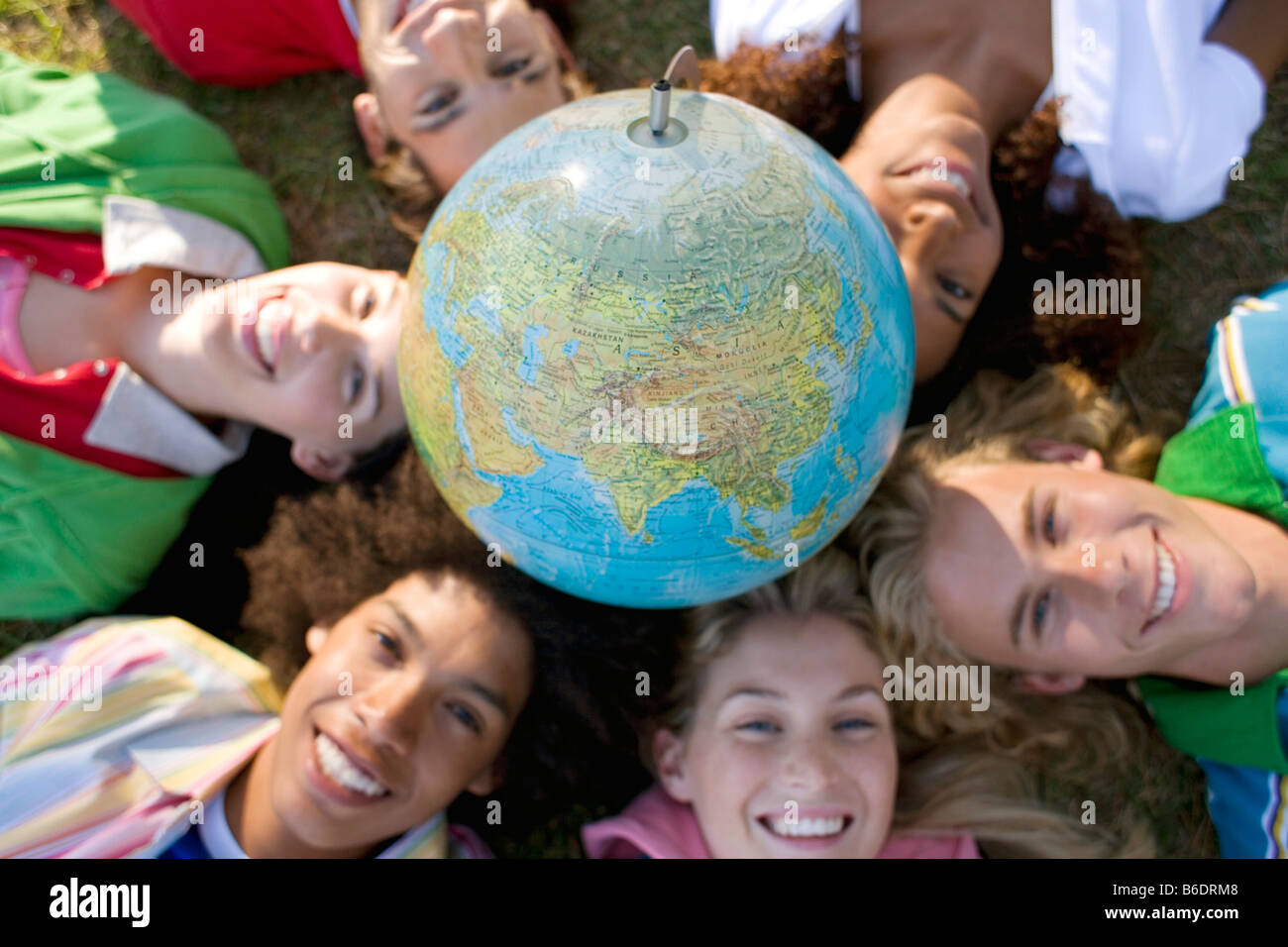 Environmental awareness. Group of friends lying down in a circle with a globe of the Earth resting on their heads. - Stock Image