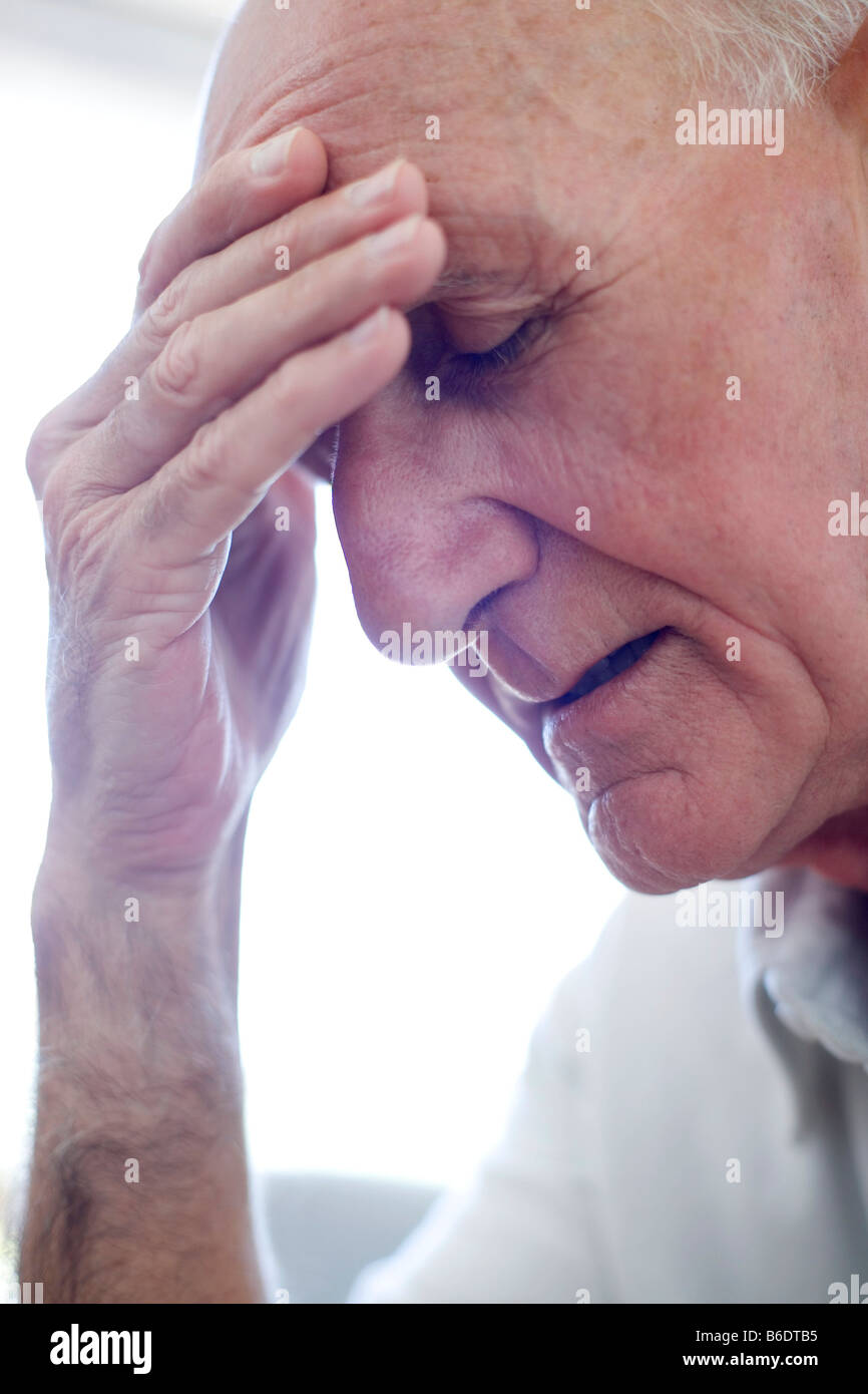 Depression. Unhappy man holding his hand to his forehead. - Stock Image