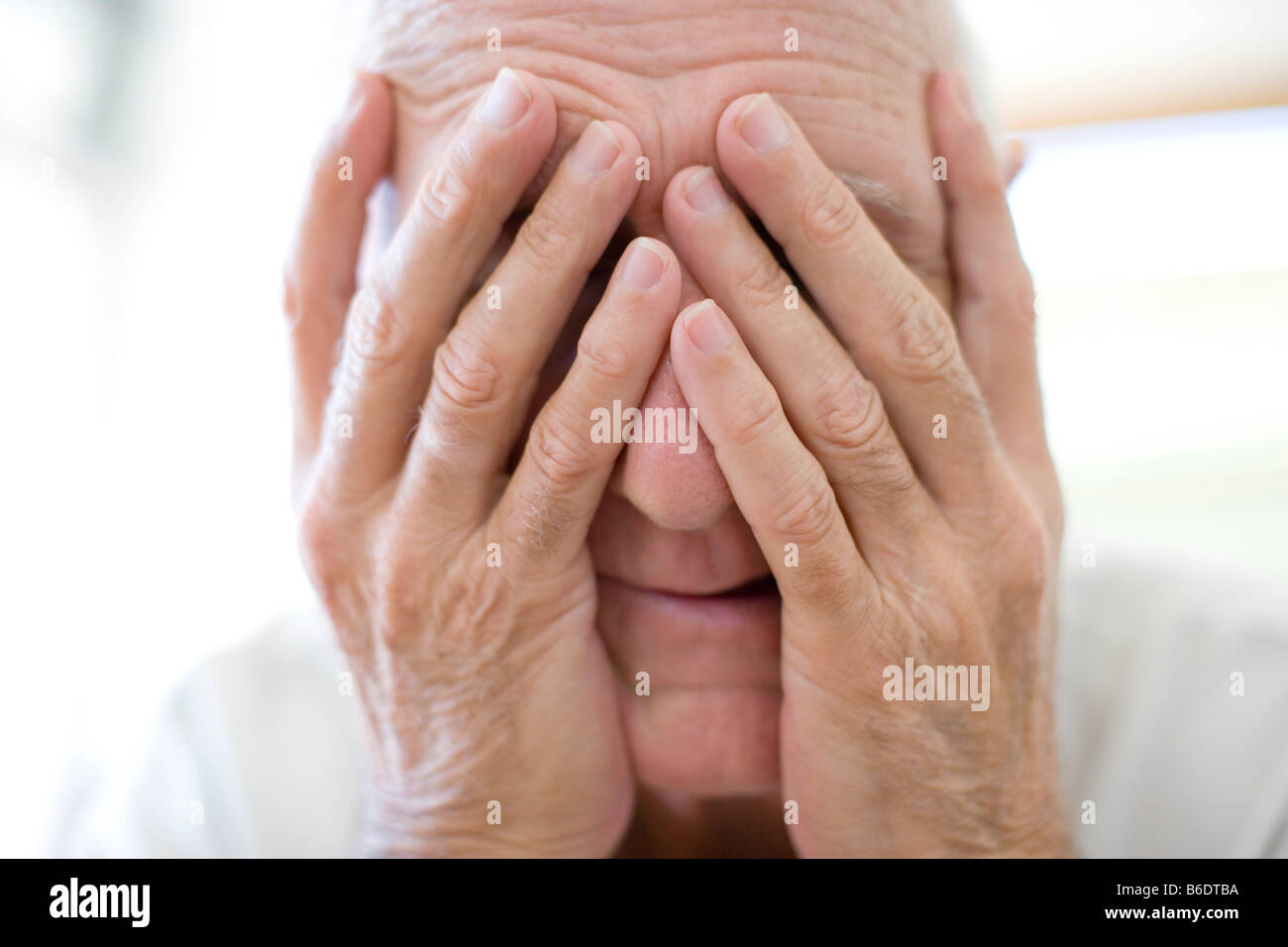 Depression. Unhappy man covering his face with his hands. - Stock Image