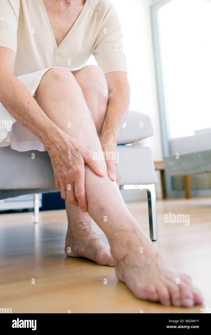 Woman rubbing her aching leg - Stock Image