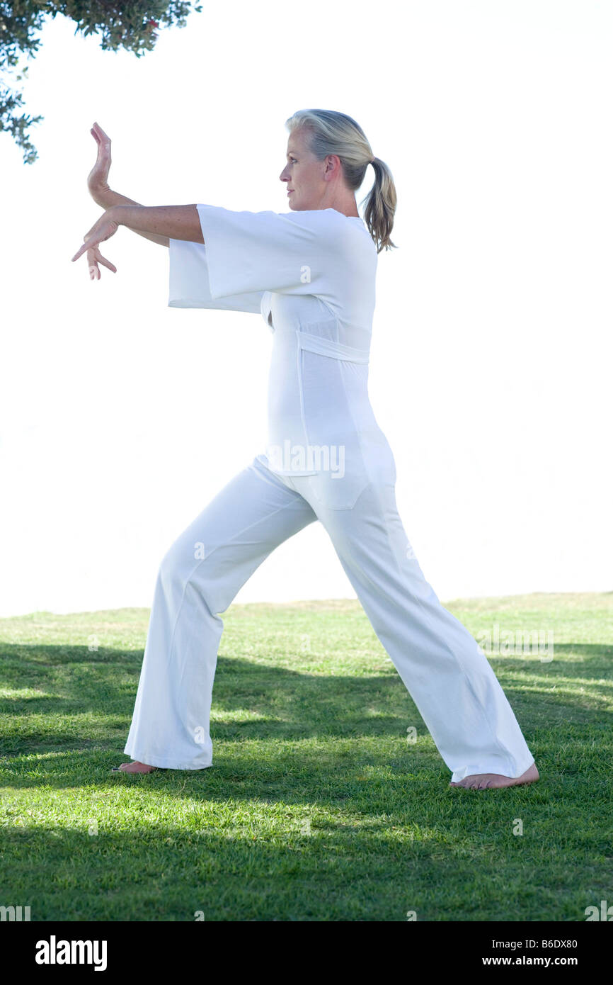 Senior woman performing Tai Chi exercise - Stock Image